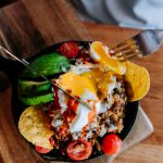 A hearty huevos rancheros skillet with spiced rice, ground beef, spinach, mushrooms, cheese mix, corn tortillas, and a poached egg drizzled with Valentina hot sauce