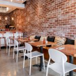 Brick wall, white chairs and coffee cushions at Monki Inglewood