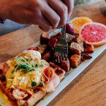 Classic Calgary breakfast Eggs benedict served on a waffle, hashbrown and fruit