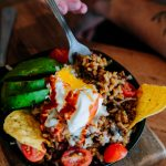 Huevos Rancheros with spiced rice, ground beef, spinach, mushrooms & tomatoes