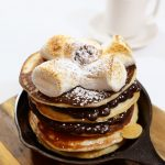 Pancakes with layers of hazelnut chocolate and fruit sauce topped with toasted marshmallows and graham crackers