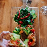 Salmon avocado toast with cherry tomatoes, cucumbers and house salad